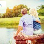 starsza para siedząca nad jeziorem