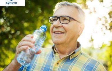 uśmiechnięty starszy pan stoi w słonecznym lesie i pije wodę z butelki